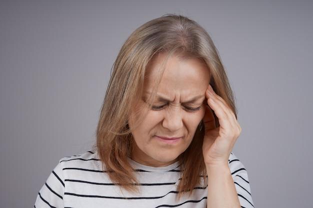 頭痛に苦しんでいる年配の女性の肖像画をクローズアップ