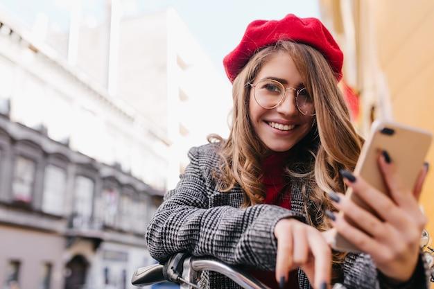 自転車に座って、大きなメガネのテキストメッセージメッセージで官能的な女の子のクローズアップの肖像画