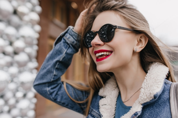 Крупным планом портрет чувственной женщины с белой кожей, улыбаясь и касаясь ее волос на улице. утонченная кавказская девушка в солнечных очках с удовольствием утром в городе.