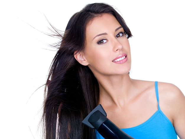 ヘアドライヤーで長い髪を乾かす官能的な美しい女性のクローズアップの肖像画