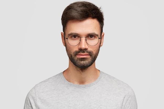 暗い剛毛で真面目な魅力的な男の学生の肖像画をクローズアップ、眼鏡をかけています