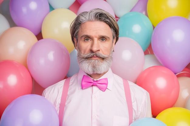Крупным планом портрет серьезного импозантного человека в праздничной одежде на воздушных шарах