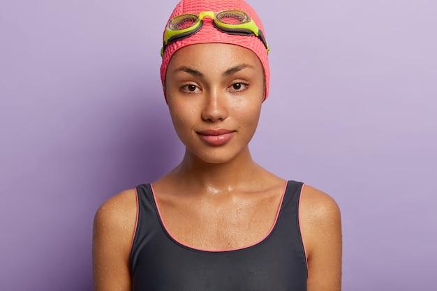 Крупным планом портрет серьезной мокрой темнокожей молодой женщины со спокойным выражением лица