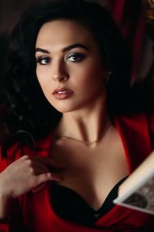 赤いドレスのセクシーな女の子の肖像画を閉じます。