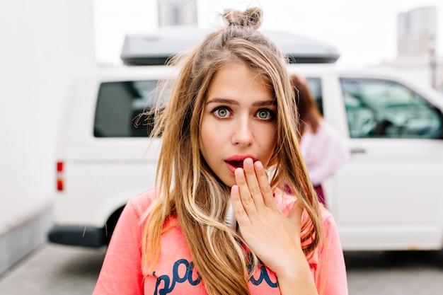 白い車の近くに立って、彼女の手で開いた口を覆っているショックを受けた若い女性のクローズアップの肖像画