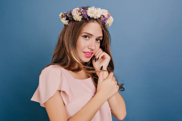 青い壁にポーズをとって花輪の恥ずかしがり屋の白人女性のクローズアップの肖像画