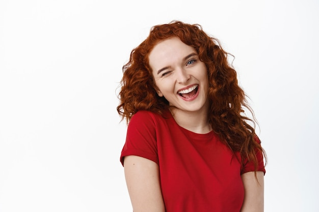 Макро портрет глупой рыжей девушки с вьющейся прической, кокетливой наклоненной головой и кокетливо подмигивающей, расслабленной и счастливой улыбающейся, стоящей в футболке у белой стены