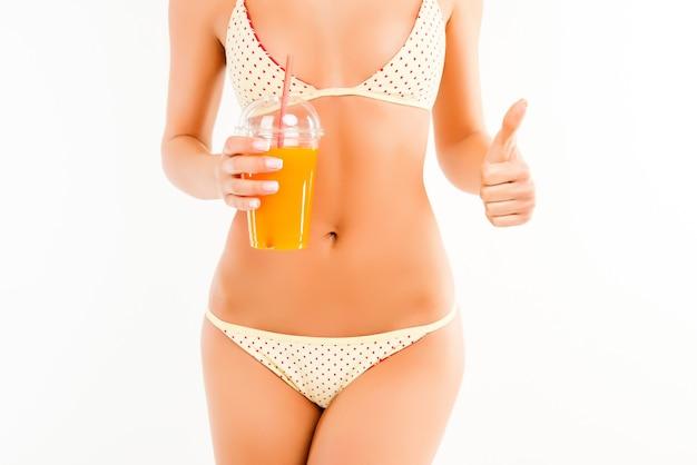 Крупным планом портрет стройной женщины в бикини с апельсиновым соком, показывая большой палец вверх