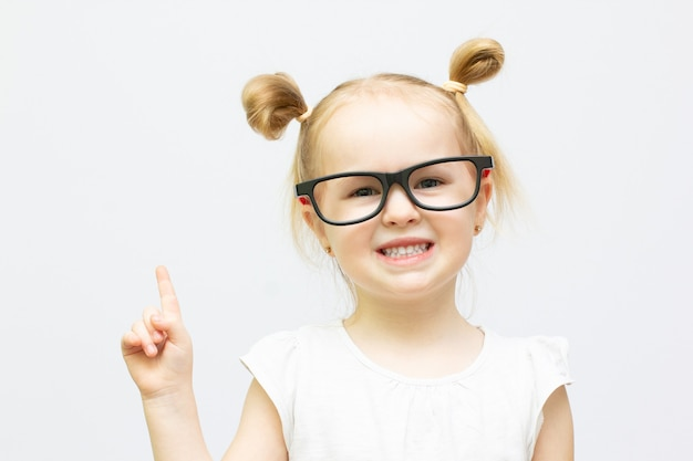 眼鏡をかけた小さなスマートな女の子のクローズアップの肖像画