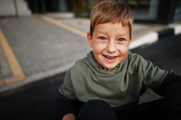 スポーツスーツを着て微笑んで座っている少年の肖像画を閉じます。