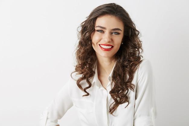 白い歯、長い巻き毛、白い口紅を着て分離されたカメラで探している赤い口紅メイクで笑顔の魅力的な女性のクローズアップの肖像画