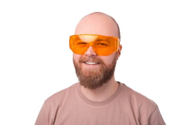 大きな黄色い眼鏡をかけている笑顔のひげを生やした流行に敏感な男の肖像画をクローズアップ