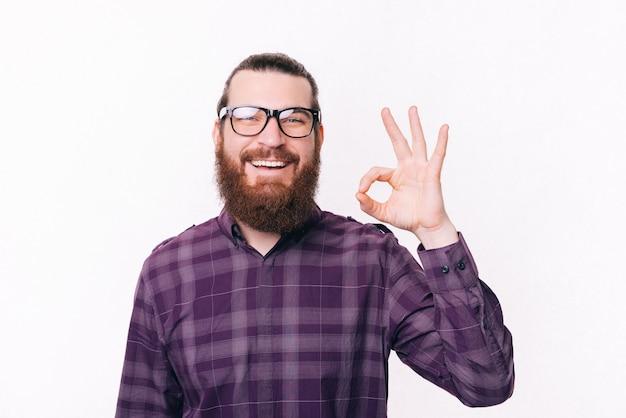 Крупным планом портрет улыбающегося бородатого хипстера в очках и показывающего жест ок