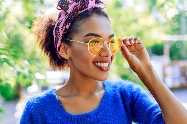 トレンディなメガネで笑顔の黒人女性の肖像画を閉じます。