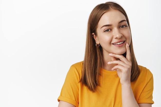 웃고 있는 금발 여성의 클로즈업 초상화는 흥미롭고 사려 깊고 흥미로운 제안을 하고 흰색 벽에 노란색 티셔츠를 입고 기쁘게 서 있습니다.