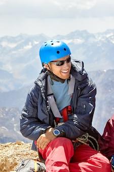 高山、ファン、パミール・アライ、タジキスタンのヘルメットで笑顔の登山家の肖像画をクローズアップ