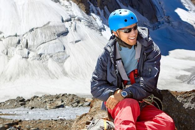 高山のヘルメットで笑顔の登山家の肖像画をクローズアップ