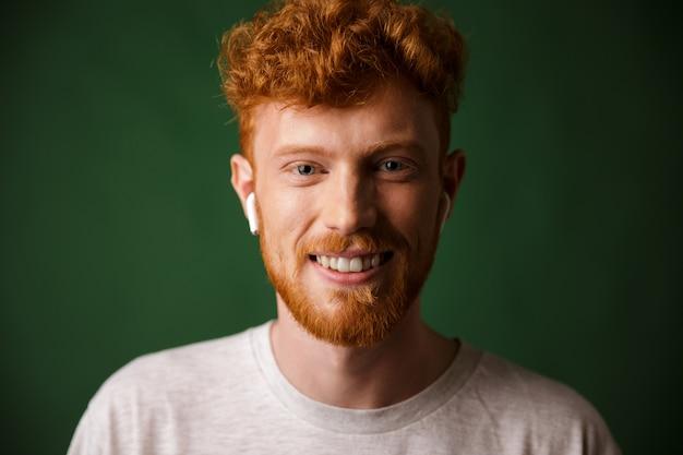 Макро портрет улыбающегося кудрявый рыжий мужчина, слушая музыку в стручках