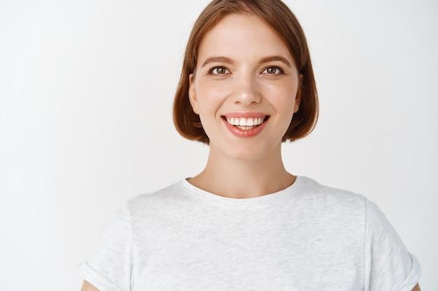 陽気に見える、短い髪とtシャツの笑顔の女の子のクローズアップの肖像画。白い壁に立っている希望に満ちた目を持つ女性