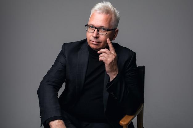 孤立した灰色の背景に立っている間、眼鏡をかけて笑っている中年のビジネスマンのクローズアップの肖像画