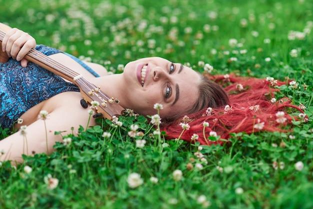 여름에 잔디에 누워 웃는 여자의 초상화를 닫습니다. 그녀의 빨간 머리는 풀밭에 흩어져 있습니다.