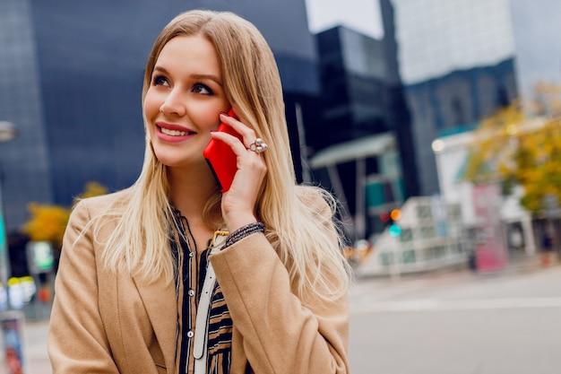 携帯電話で話している笑顔の女性の肖像画を間近します。スマートフォンを使用して成功したビジネスの女性。スタイリッシュなアクセサリー。ベージュのコート。都市の建物