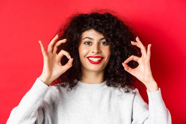 巻き毛と赤い唇を持つ笑顔の女性のクローズアップの肖像画、大丈夫なジェスチャーを示し、満足しているように見え、赤い背景の上に立って、良い製品を賞賛します。