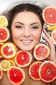 浴室で多くのジューシーな柑橘系フルーツレモングレープフルーツと笑顔の女性の肖像画間近します。