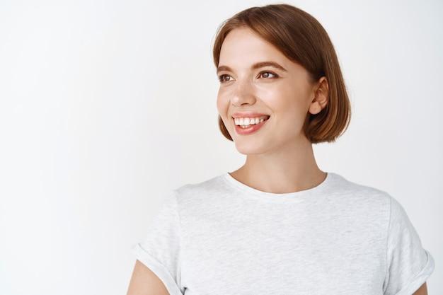 短い髪と自然光のメイクで笑顔の女性の肖像画をクローズアップ、空のスペースを脇に見て、白い壁にtシャツで立っている