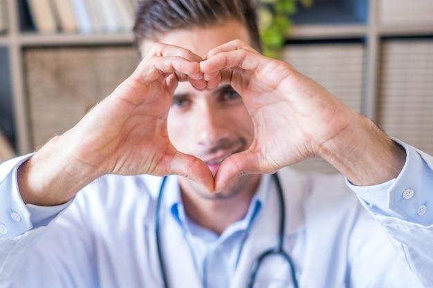 웃고 있는 백인 남성 간호사나 흰색 의료복을 입은 gp의 초상화를 클로즈업하여 하트 러브 손 제스처를 보여줍니다. 행복한 젊은 남자 의사는 병원에 있는 환자나 고객에게 지원과 보살핌을 보여줍니다.