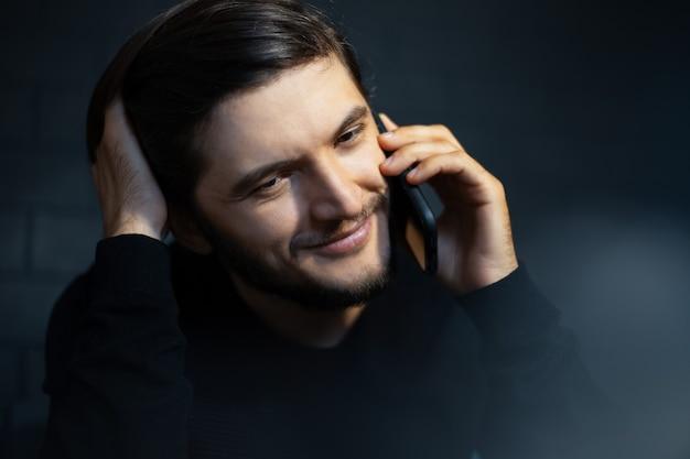 スマートフォンで話している笑顔の若い男のクローズアップの肖像画。
