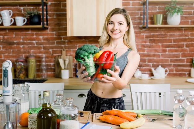 Портрет конца-вверх усмехаясь молодой женщины держа стеклянный шар с свежими овощами пока стоящ на таблице с здоровой едой в современной кухне. концепция здорового питания