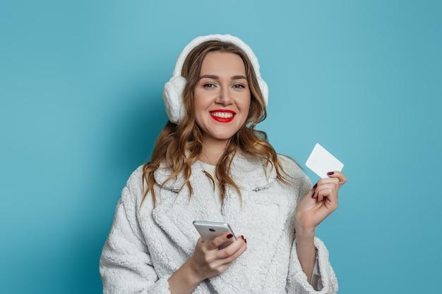 Крупным планом портрет улыбающейся молодой женщины в зимней белой шубе, держащей мобильный телефон и кредитную банковскую карту, изолированную на синей стене