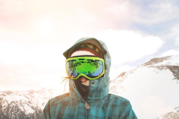 日没と雪山の前でポーズをとるスノーボーダーの肖像画をクローズアップ