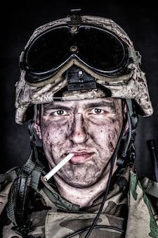 특수 부대 군인, 헬멧에 탄도 고글을 쓴 미 해병대 보병의 초상화를 닫고, 검은 배경에 입 스튜디오 촬영에서 더러운 얼굴과 담배를 들고 있습니다. 전쟁 참전 용사