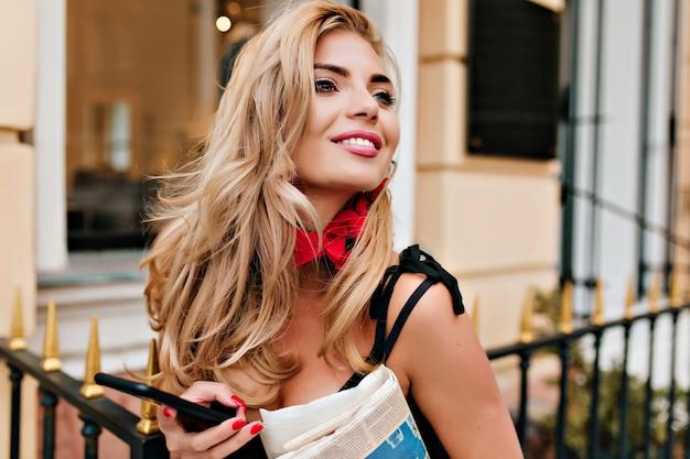 Крупным планом портрет эффектной женщины со светлыми блестящими волосами, глядя вверх и смеясь возле ресторана
