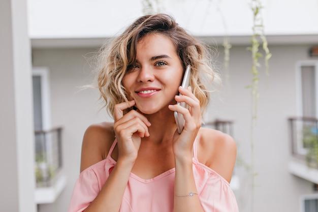 電話での会話中に彼女の顔に触れているピンクのブラウスの壮大な若い女性のクローズアップの肖像画。ホテルのバルコニーから友達を呼んでいるかわいいブロンドの女の子。