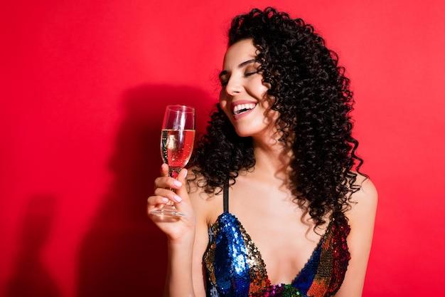 Крупным планом портрет потрясающей веселой волнистой девушки, пьющей вино, наслаждающейся ночной жизнью, изолированной на фоне сияющего красного цвета