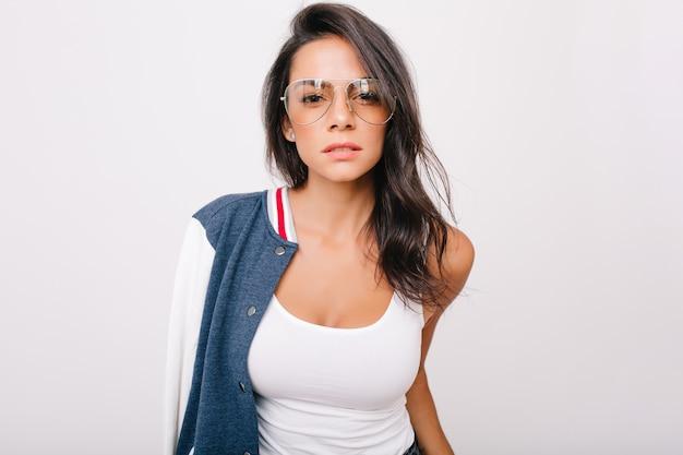 興味を持って見ている白いタンクトップの見事な黒髪の少女のクローズアップの肖像画。スタイリッシュなメガネで身も凍るような愛らしいヨーロッパの女性の屋内写真