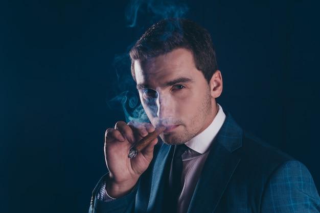 葉巻を吸っている見事な男の肖像画をクローズアップ
