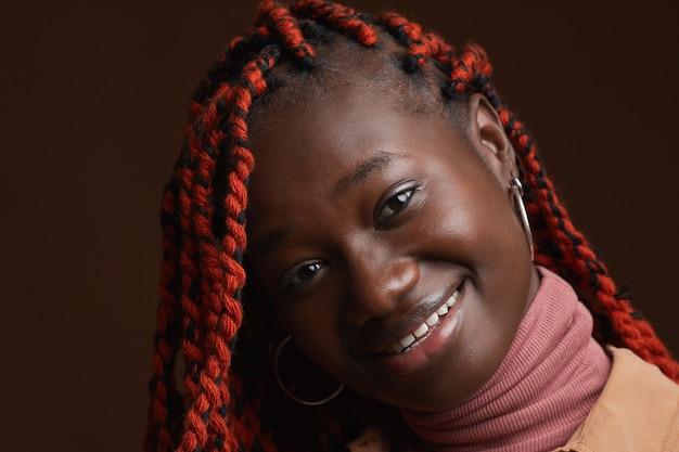 スタジオでダークブラウンの背景にポーズをとっている間幸せに笑っている編みこみの髪を持つスタイリッシュなアフリカ系アメリカ人女性の肖像画をクローズアップ