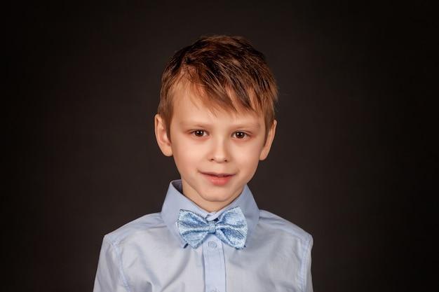 黒の背景に、スタイリッシュな子、7歳の面白い小さな男の子のクローズアップの肖像画。自信を持って陽気な笑顔で青いシャツと蝶ネクタイのかわいい愛らしい男子生徒の孤立した画像。コピースペース