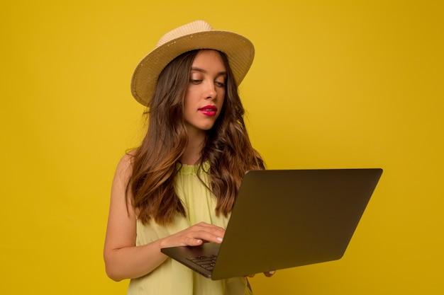 孤立した壁の上のラップトップを使用して長いウェーブのかかった髪の帽子をかぶっているスタイリッシュな女の子のクローズアップの肖像画