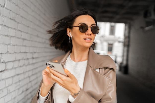 캐주얼 가죽 코트에 이어폰을 끼고 스마트폰을 사용하고 도시 벽돌 벽 위에 포즈를 취한 선글라스를 쓴 세련된 짧은 머리 여성의 초상화를 클로즈업