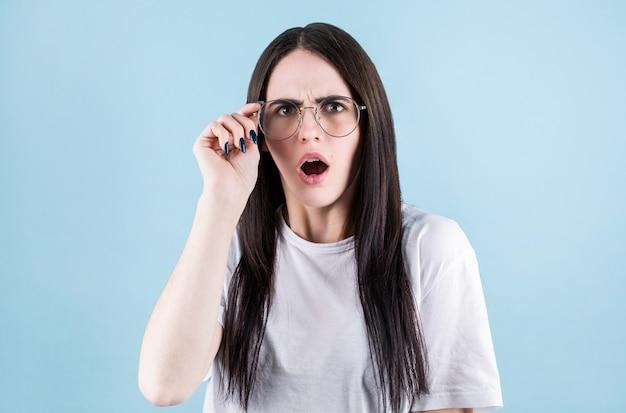 Крупным планом портрет удивленной девушки в белой футболке, касающейся ее очков, изолированных на синем фоне копией пространства