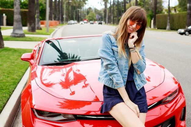 カリフォルニアの驚くべき赤いコンバーチブル車のボンネットの上に座って驚いたブルネットの女性の肖像画を間近します。