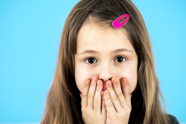 파란색 배경에 분홍색 머리핀을 가진 놀란 귀여운 소녀의 초상화를 닫습니다.
