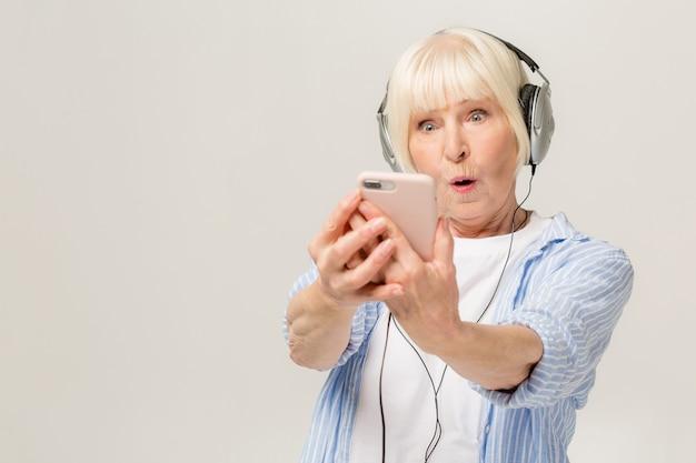 흰색 배경에 고립 된 인터넷을 통해 화상 통화를 갖는 할머니 할머니 할머니와 놀란 흥분된 유쾌의 초상화를 닫습니다.