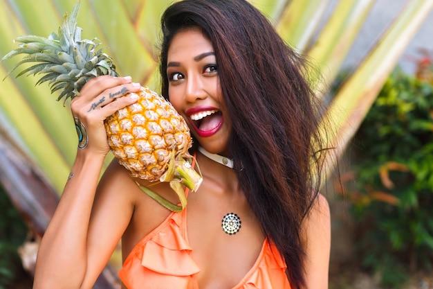 ビキニを着て指の入れ墨を持つ日焼けしたアジアの女の子のクローズアップの肖像画。背景にパイナップルを押しながらヤシの木と笑っているかなりラテンの若い女性。