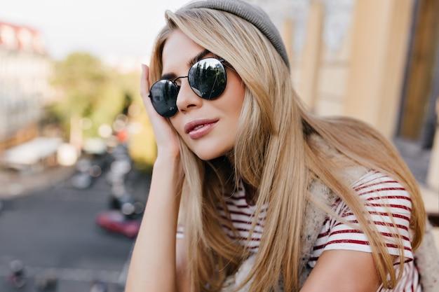 暗い眼鏡を通して目をそらしているエレガントな髪型を持つ日焼けしたヨーロッパの女性のクローズアップの肖像画